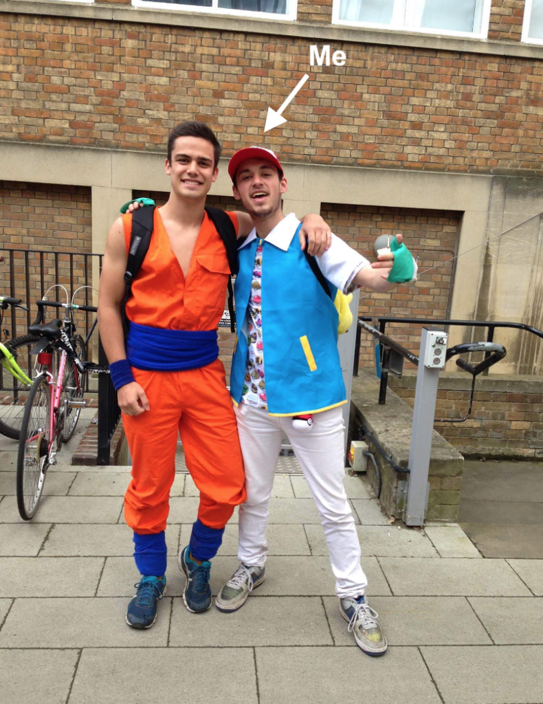 Two students hugging in new museums site near the bicycle racks. On the left, a guy is dressed as Goku from Dragon ball Z in a bright orange jumpsuit with navy bands around their waist, wrists and ankles. On the right, a guy is dressed as Ash Ketchum from Pokémon in a blue jacket, green gloves, a red cap and poke balls covering their T shirt. A white arrow labelled with the text 'Me' points to the guy dressed as Ash Ketchum on the right