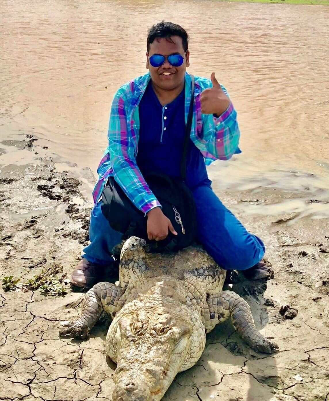 Image may contain: Apparel, Clothing, Alligator, Reptile, Crocodile, Sunglasses, Accessory, Accessories, Glasses, Nature, Outdoors, Sand, Animal, Human, Person