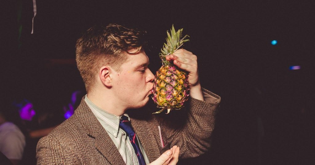 Image may contain: Finger, Overcoat, Apparel, Clothing, Coat, Suit, Person, Human, Accessories, Accessory, Tie, Fruit, Plant, Pineapple, Food
