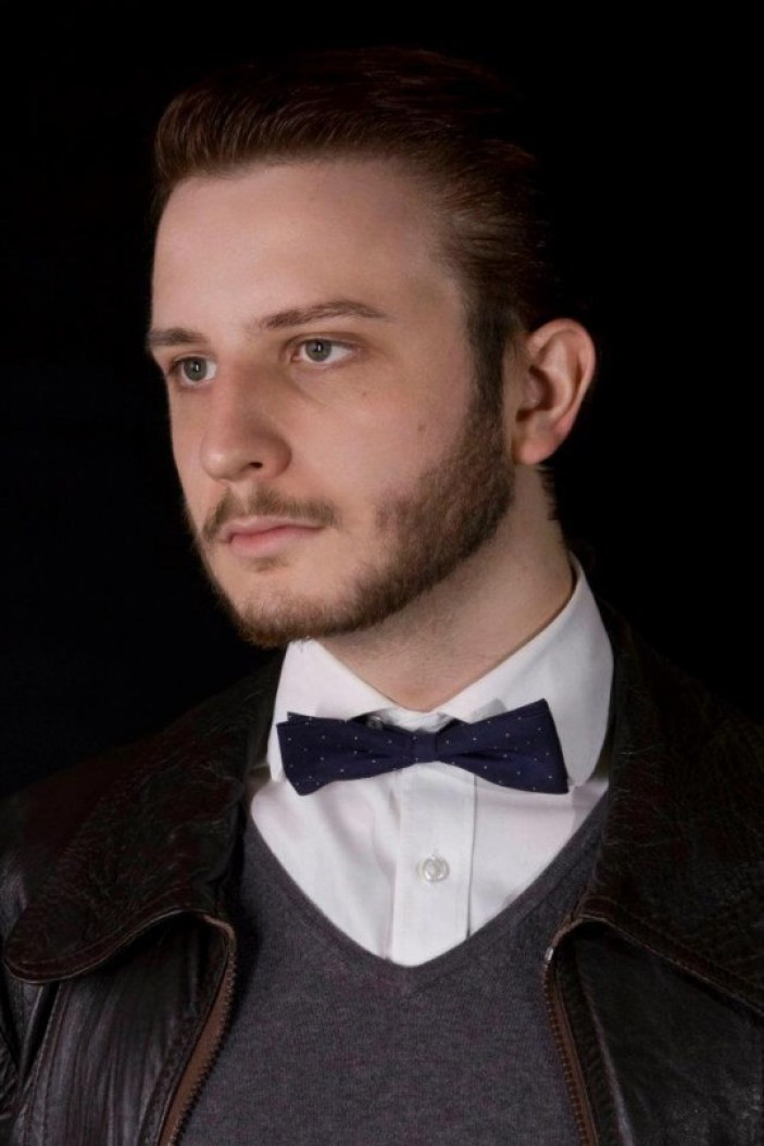 In a professional photo, Jack Buckby looks forlornly into the distance. He wears a shirt, jumper and bow tie underneath a leather bomber jacket