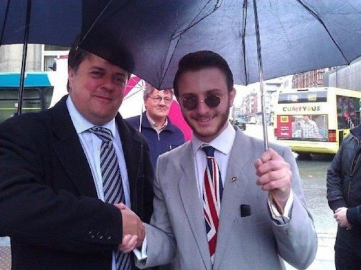 Jack Buckby stands next to Nick Griffin under an umbrella. Buckby sports John Lennon-esque glasses and a Union Jack tie. Nick Griffin's head rubs against the edge of their umbrella