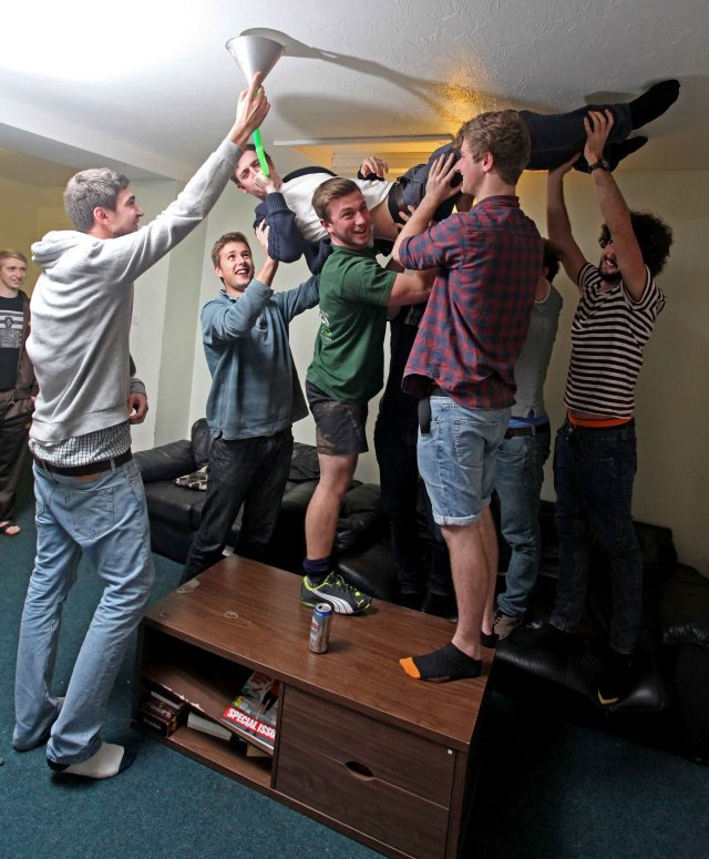 George Streets downs a beer bong whilst doing a 'Starfish' on the ceiling, at the Regent House in Plymouth, Devon. Regent house is the biggest student house in the UK, and is home to 32 students. See swns story SWSTUDENT - Home to 32 students, 22 toilets, a pool table, five fridges and seven showers, this is Britain's biggest student house. Situated in the heart of Plymouth's student suburb, Regent House is comprised of three large terrace town houses knocked into one. Made up of eight females and 24 males, the house needs three cleaners six days a week to keep on top of the mess. The students, which come from countries across the globe and are aged between 18 - 24, study subjects ranging from civil engineering, to fine art to business to midwifery. On average per week the students get through around 40 loo rolls, 20 bin bags of rubbish, 100 tins of baked beans and 500 cans of beer, 150 cans of cider, 50 Pot Noddles, 150 takeaways. Largely first years. Supposed to 320 hours a week at uni - each watch on average 42 hours a week TV (1,300 hours total) and play 28 hours Playstation each (a total of 900 (hours). Pay 75 - 100 per week