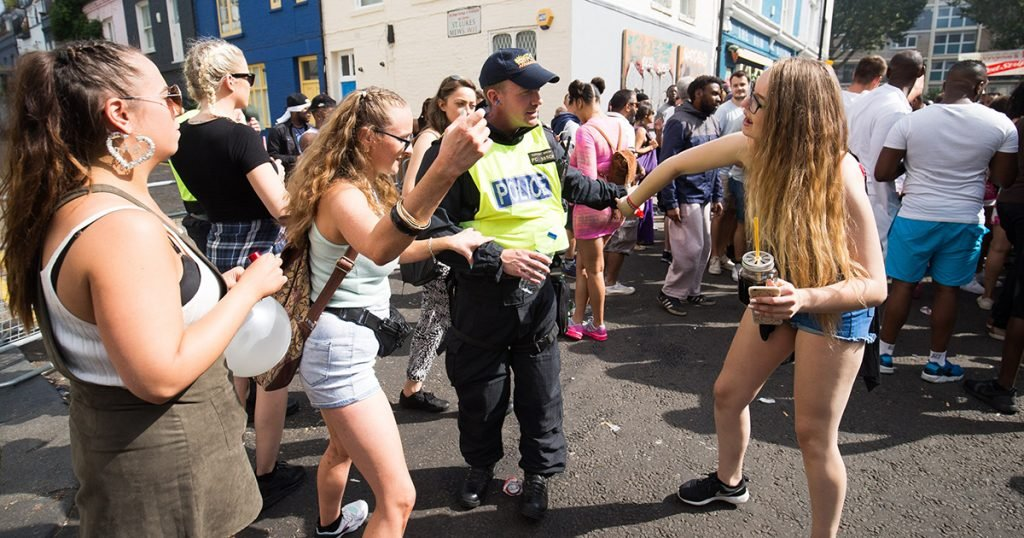 Girls dance with a police officer at Notting Hill Carnival, London. 29 August 2016.