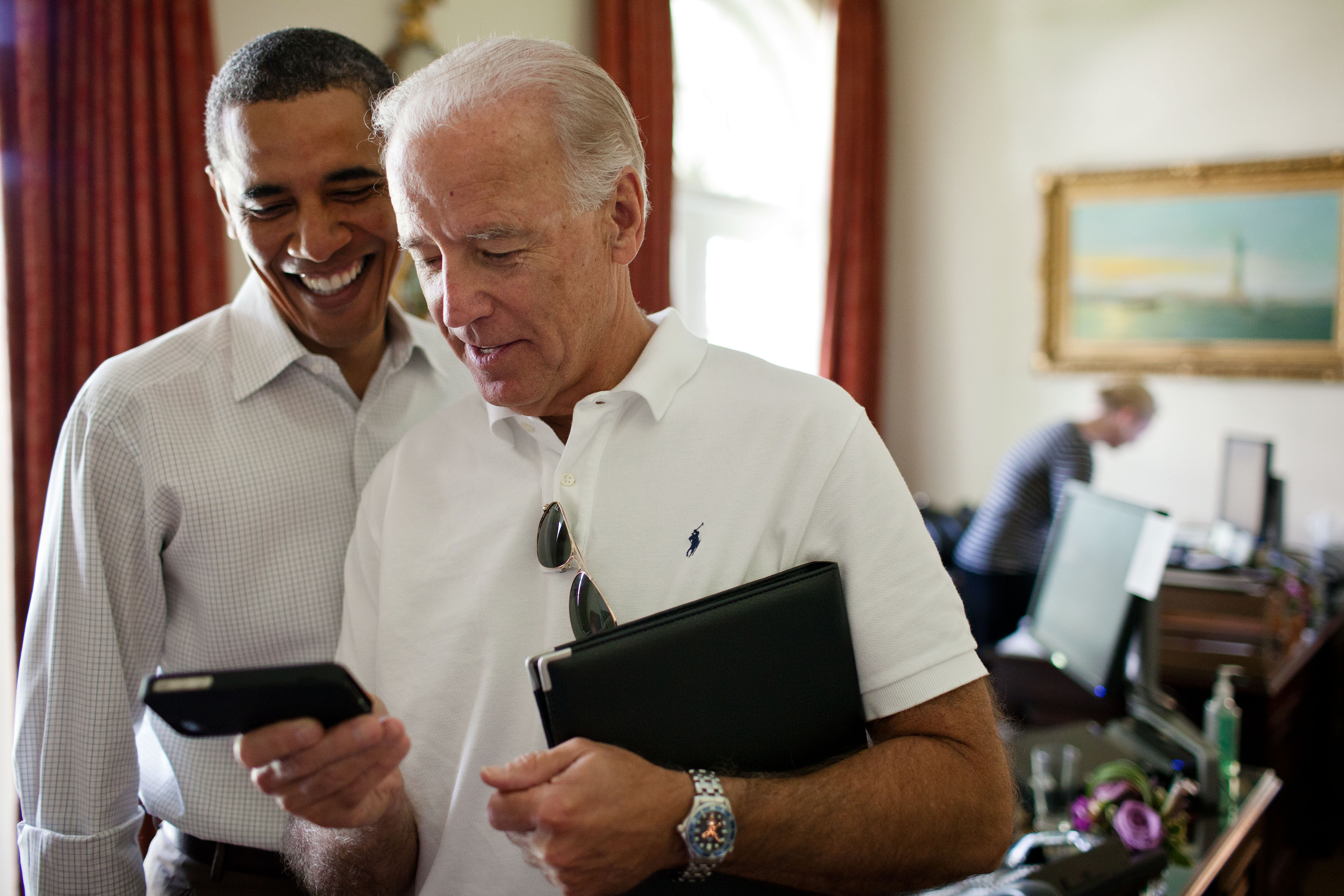 Vice President Joe Biden and President Barack Obama look at an app on an iPhone in the Outer Oval Office, Saturday, July 16, 2011. (Official White House Photo by Pete Souza) This official White House photograph is being made available only for publication by news organizations and/or for personal use printing by the subject(s) of the photograph. The photograph may not be manipulated in any way and may not be used in commercial or political materials, advertisements, emails, products, promotions that in any way suggests approval or endorsement of the President, the First Family, or the White House.