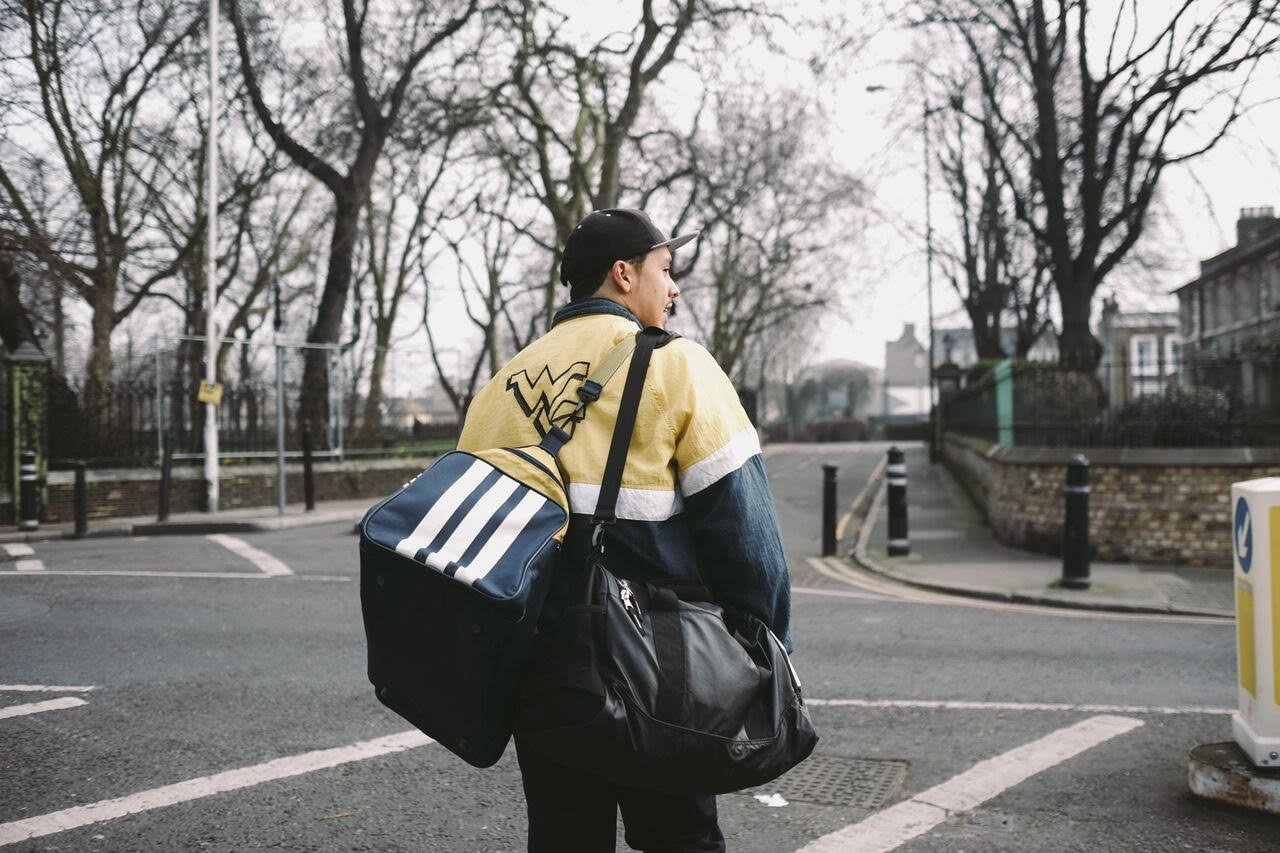 A young man with vintage sportswear and two sportsbags walks across a quiet empty road in London