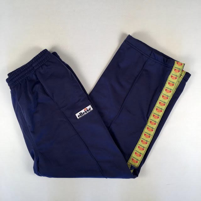 8a1508cad445ce A picture of navy Ellesse tracksuit bottoms, folded in half on a plain  white table