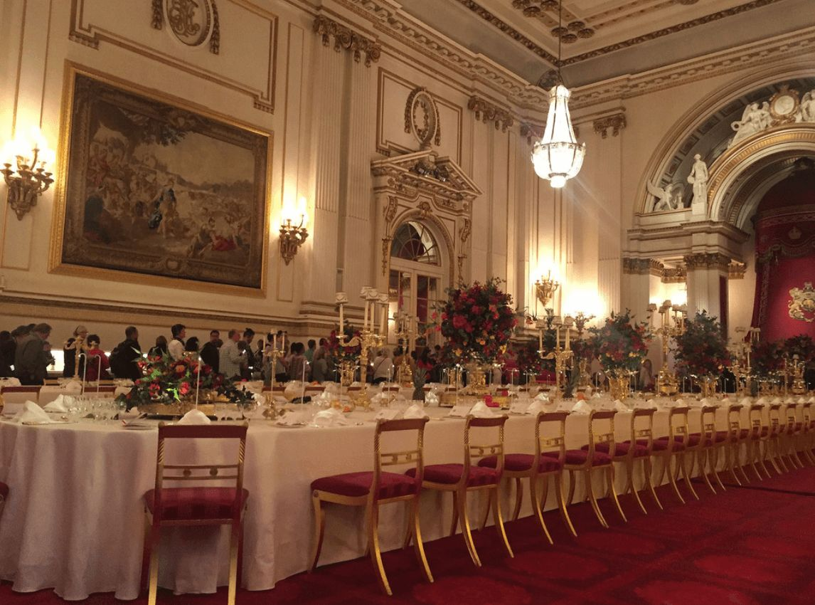 Image may contain: What does the Queen eat, meals, food, menu, pizza, takeaway, royal family, buckingham palace, the Queen, kitchen staff, Interior Design, Dining Room, Worship, Church, Cathedral, Building, Architecture, Altar, Waiting Room, Room, Reception Room, Reception, Indoors, Table, Furniture, Dining Table, Suitcase, Luggage