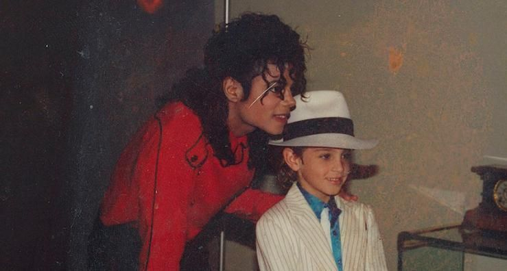 Image may contain: Michael Jackson Estate, Michael Jackson net worth, Leaving Neverland, Michael Jackson, money, earnings, Wade Robson, Suit, Overcoat, Accessory, Accessories, Glasses, Coat, Man, Hair, Photography, Photo, Portrait, Smile, Dating, Blonde, Child, Kid, Girl, Teen, Woman, Hat, Female, Human, Person, Face, Clothing, Apparel