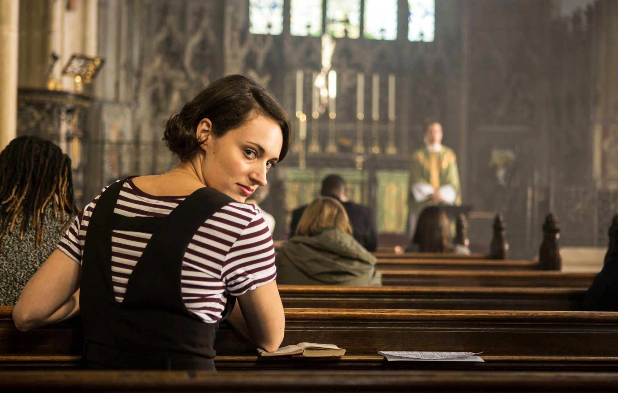 Image may contain: Fleabag hidden meanings, Fleabag, Female, Worship, Indoors, Sitting, Wood, Person, Human