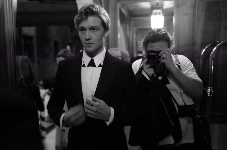 Image may contain: who is Joe Alwyn, Joe Alwyn, Taylor Swift boyfriend, engagement, Taylor Swift, Photo, Photography, Tuxedo, Camera, Electronics, Photographer, Accessory, Accessories, Tie, Apparel, Coat, Suit, Clothing, Overcoat, Human, Person