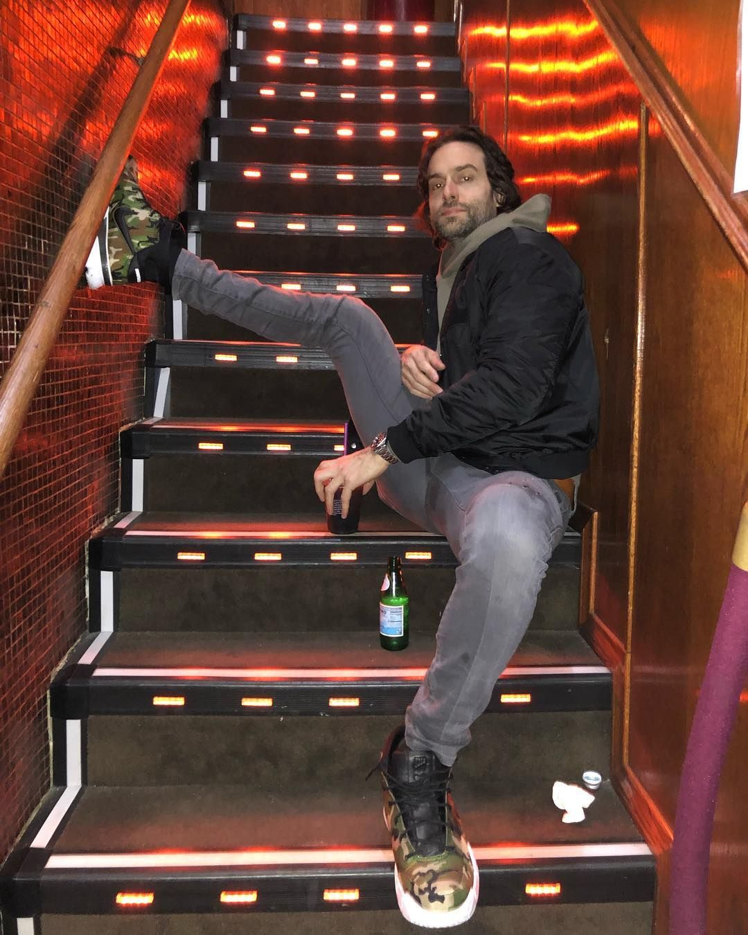 Image may contain: You season 2 cast, cast list, You, Netflix, season 2, Chris D'Elia, Henderson, Boot, Staircase, Human, Person, Banister, Handrail, Shoe, Apparel, Footwear, Clothing