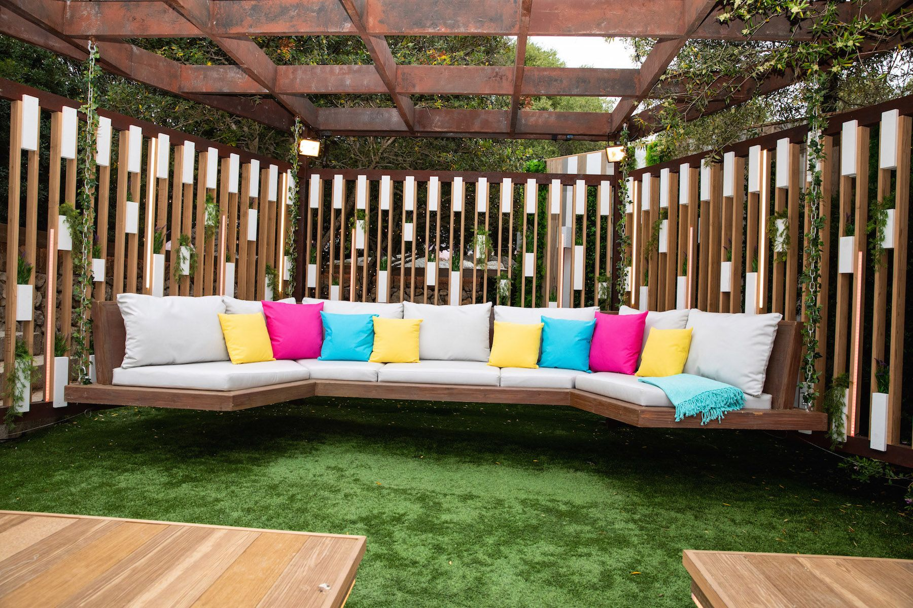 Image may contain: Love Island villa, 2019, location, Couch, Wood, Table, Outdoors, Pillow, Pergola, Furniture, Cushion, Patio, Porch