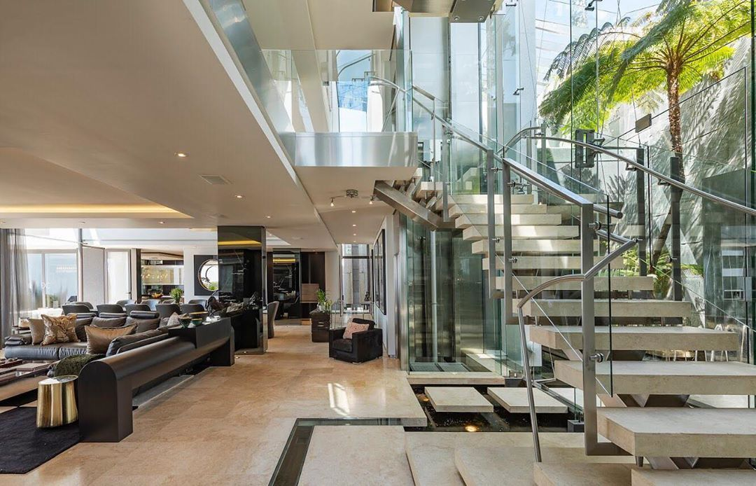 Image may contain: Moondance Villa, Made in Chelsea, Cape Town, South Africa, cost, book, MIC, price, location, Flooring, Table, Staircase, Furniture, Living Room, Housing, Building, Lobby, Indoors, Room