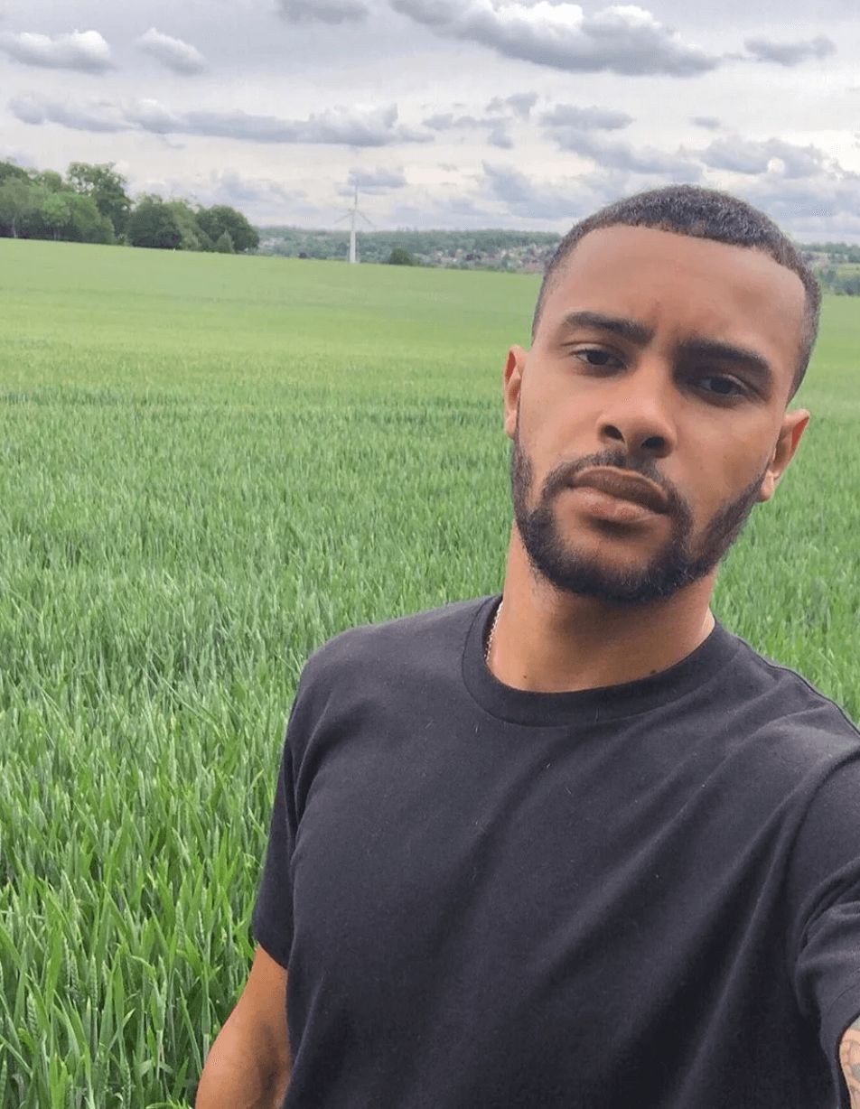 Image may contain: Casa Amor cast, Casa Amor, Love Island, Dennon Lewis, contestant, cast, Islander, new, boy, Instagram, age, job, Rural, Vegetation, Beard, Land, Man, Countryside, Grassland, Grass, Plant, Face, Field, Outdoors, Nature, Person, Human