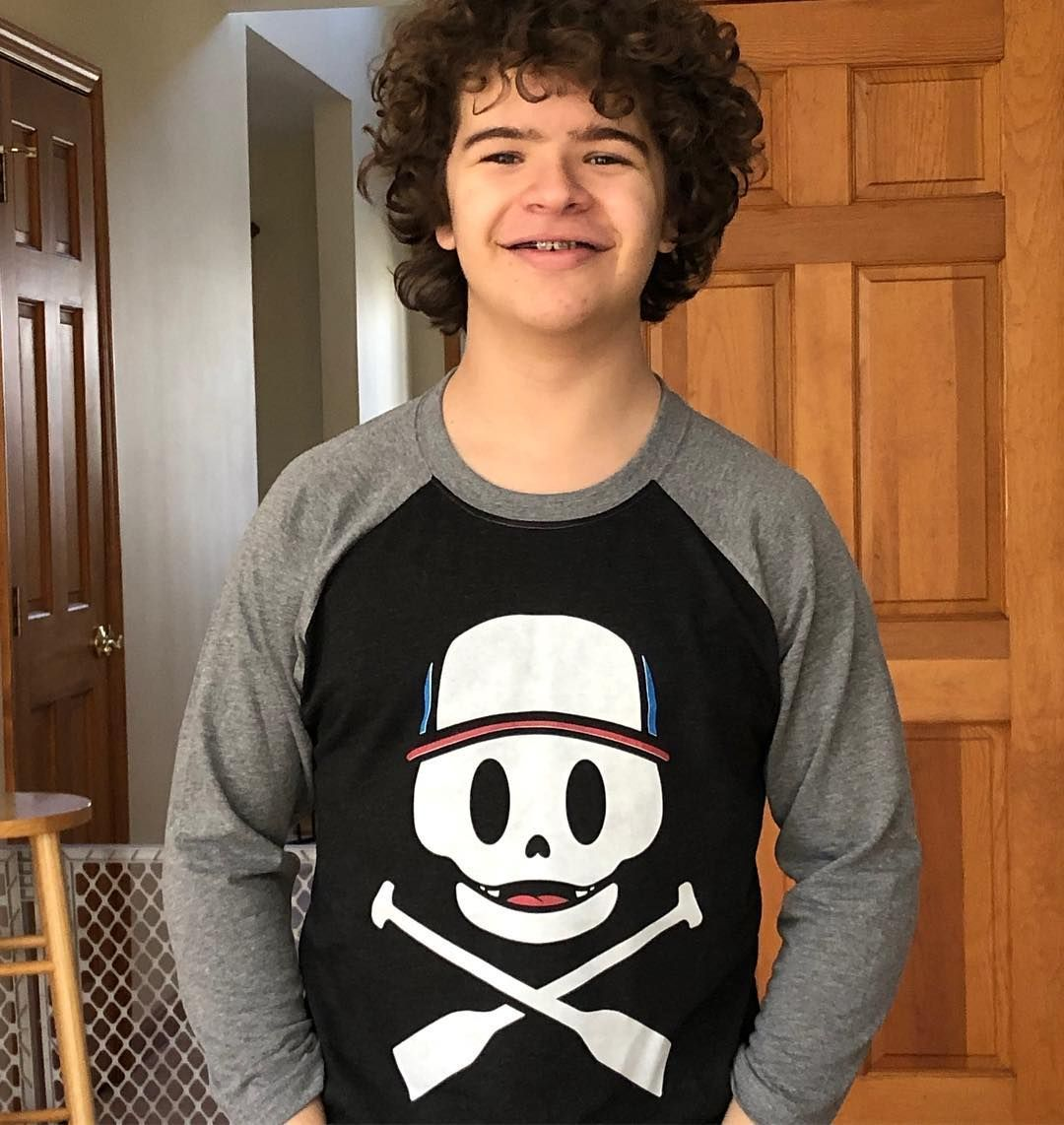 Image may contain:  Stranger Things cast ages, Stranger Things, 3, cast, age, old, birthday, Gaten Matarazzo, Dustin, Hair, Long Sleeve, Face, Sweatshirt, Hoodie, Sweater, Wood, Person, Human, Sleeve, Apparel, Clothing