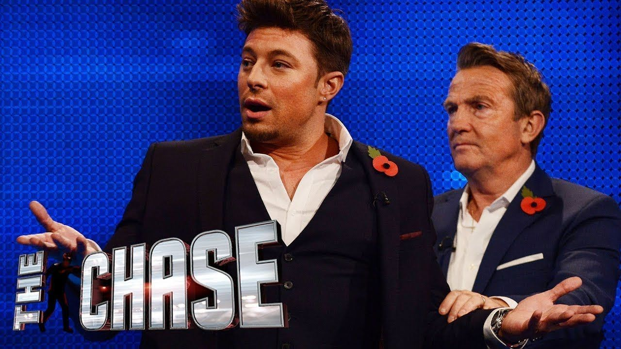Image may contain: The Chase biggest wins, The Chase, ITV, Celebrity chase, Duncan James, Bradley Walsh, prize, fund, winners, money, cash, final, builder, chaser, Home Decor, Audience, Overcoat, Coat, Suit, Clothing, Apparel, Crowd, Human, Person