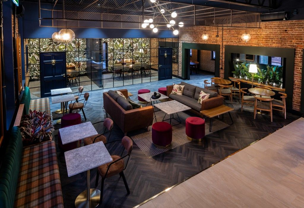 Image may contain: Hotel, Person, Human, Home Decor, Wood, Building, Table, Chair, Couch, Living Room, Interior Design, Furniture, Indoors, Room, Lobby