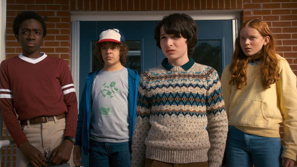 Image may contain: Stranger Things recap, season one, two, three, Stranger Things 3, episodes, recap, what happened, the gang, Eleven, Hawkins, Long Sleeve, Sweatshirt, Pants, Hat, Sweater, Sleeve, Person, Human, Clothing, Apparel