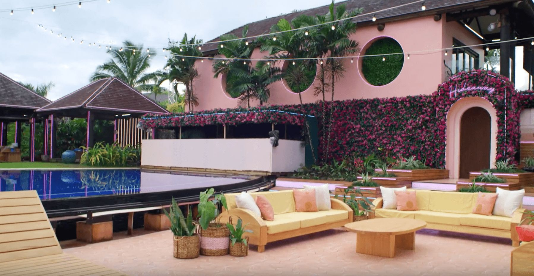 Image may contain: Love Island USA villa, Love Island USA, villa, Love Island, CBS, outside, decking, seating, lounge, palm trees, Fiji, Hideaway, Room, Patio, Indoors, Building, Hotel, Plant, Table, Furniture, Couch