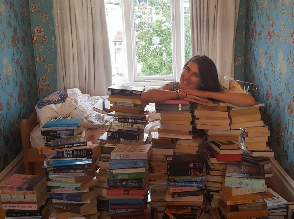 Image may contain: Shelf, Bookcase, Book, Library, Interior Design, Human, Person, Room, Indoors, Furniture