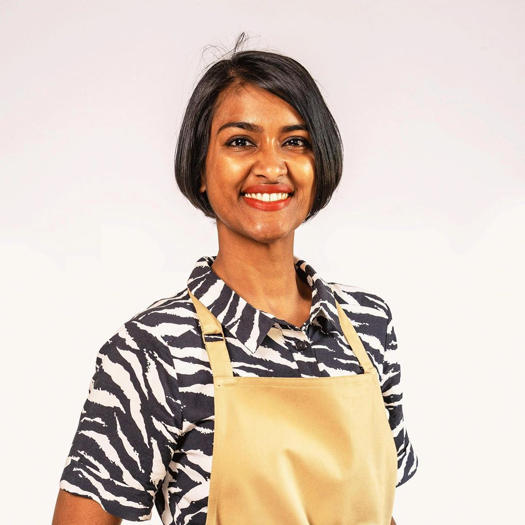Image may contain: Great British Bake Off 2019, Priya O'Shea, Priya, cast, contestants, lineup, Instagram, GBBO, Bake Off, 2019, start date, Channel 4, Female, Apron, Face, Sleeve, Apparel, Clothing, Human, Person
