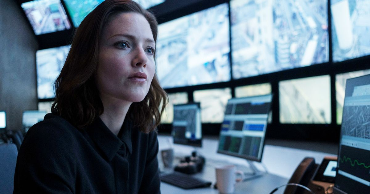 Image may contain: The Capture cast, The Capture, BBC, One, Holliday Grainger, Rachel Carey, Computer, Pc, Laptop, Desk, Furniture, Table, LCD Screen, Monitor, Electronics, Display, Screen, Human, Person
