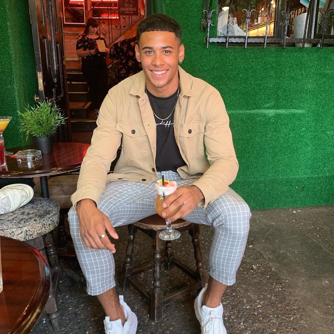 Image may contain: first winter Love Island contestant, winter, Love Island, Ellis Iyayi, 2020, cape town, south africa, contestant, cast, lineup, rumours, fitness, instructor, man, boy, new, Pub, Bar Counter, Pants, Long Sleeve, Sleeve, Restaurant, Plywood, Wood, Sitting, Shoe, Footwear, Human, Person, Clothing, Apparel