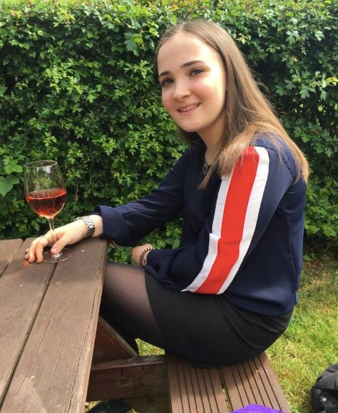 Image may contain: Pants, Red Wine, Kid, Girl, Child, Teen, Blonde, Wine Glass, Nature, Yard, Vegetation, Plant, Apparel, Clothing, Outdoors, Woman, Glass, Wine, Drink, Beverage, Alcohol, Human, Person, Female