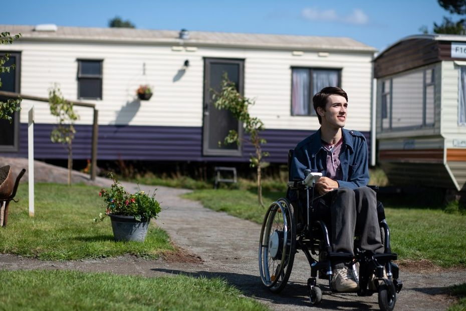 Image may contain: Urban, Neighborhood, Wheel, Machine, Mobile Home, Human, Person, Building, Housing, Chair, Furniture, sex education season two new cast, george robinson, isaac, netflix