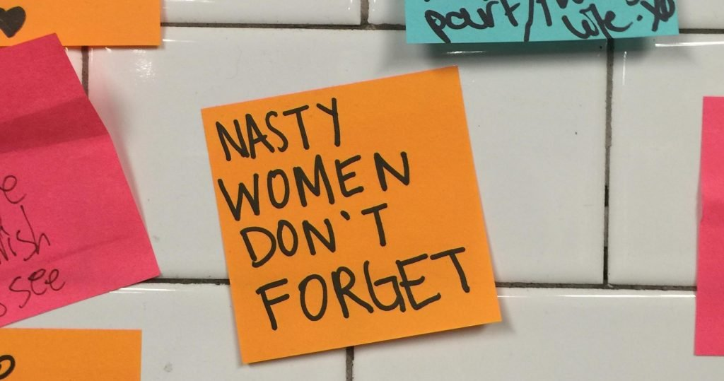 Nasty women dont forget - a post it note on the new york subway