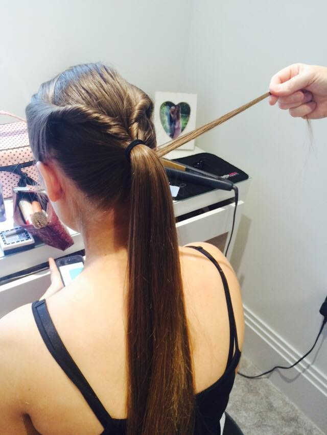 Take a small section of hair from the ponytail and wrap around the band to disguise it.