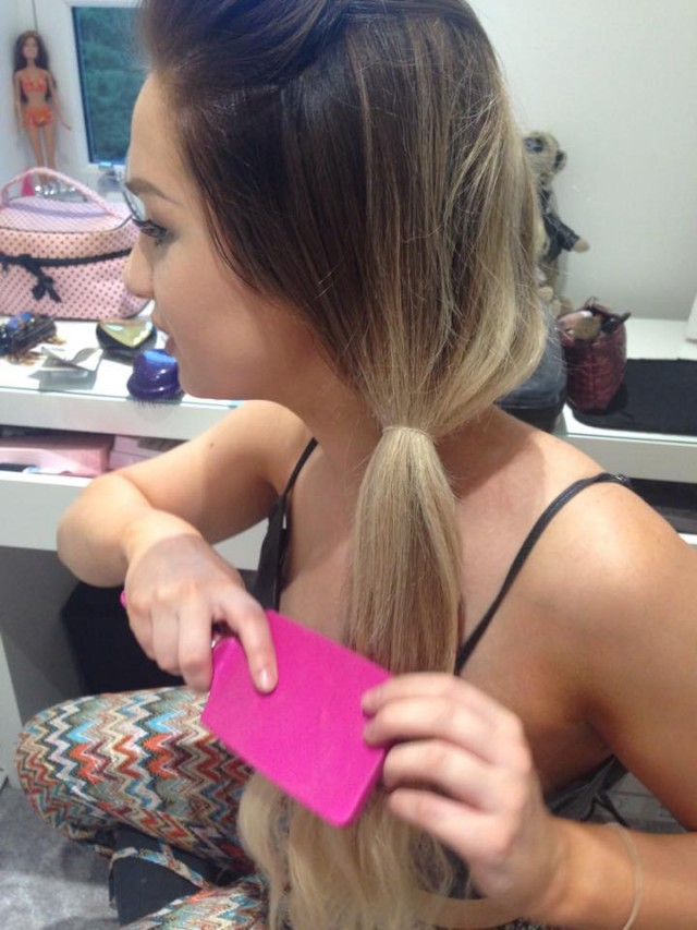 Secure into a side pony with a clear band and brush through the hair.