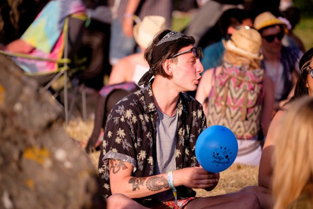 People inhale NOS ballons (aka hippy crack) as the sun sets at Glastonbury Festival 2015, on Worthy Farm, Somerset. June 25 2015.  See SWNS story SWGLASTO; Glastonbury is the largest greenfield festival in the world, and is now attended by around 175,000 people requiring extensive infrastructure in terms of security, transport, water, and electricity supply. The majority of staff are volunteers, helping the festival to raise millions of pounds for good causes.