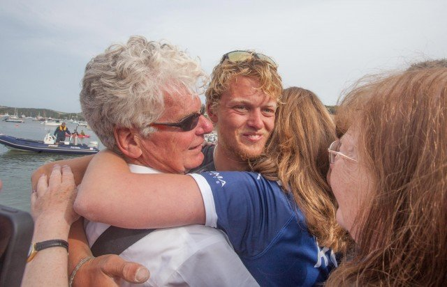 Tom Rainey is hugged as he steps back onto dry land