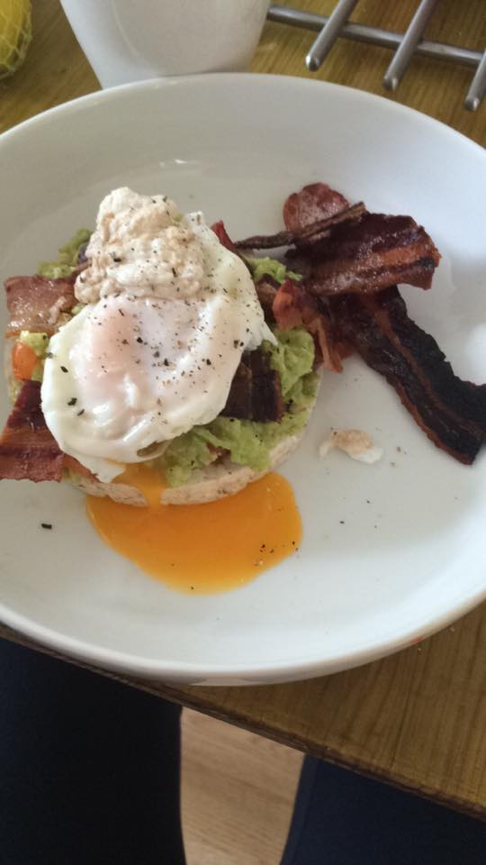 Eleni's guacamole on a rice cake with a poached egg and bacon