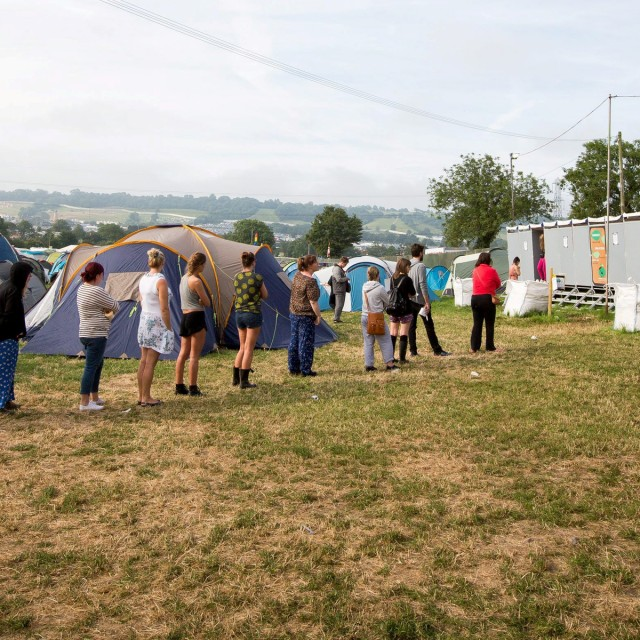 Festival goers use the toilet facilities at Glastonbury Festival, Worthy Farm in Pilton, Somerset. See SWNS story SWWEE: The organisers of Glastonbury Festival are being prosecuted over their handling of human sewage - because of the number of people weeing in HEDGES. Local councillors claim the festival has failed to meet environmental requirements when dealing with the gallons of urine produced by music lovers during the week-long event. The Environment Agency, which monitors a stream flowing through the site, is prosecuting the company on the grounds that it breached regulations in 2014. It is believed the number of people weeing in the hedges have impacted the on pollution levels in the stream during the 2014 festival, which attracted almost 200,000 revellers.