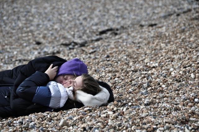 brighton beach couple lying down on pebbles